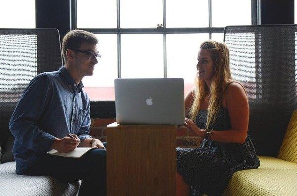 Une jeune femme blonde montre des blogs sympas sur son ordi à un jeune homme.