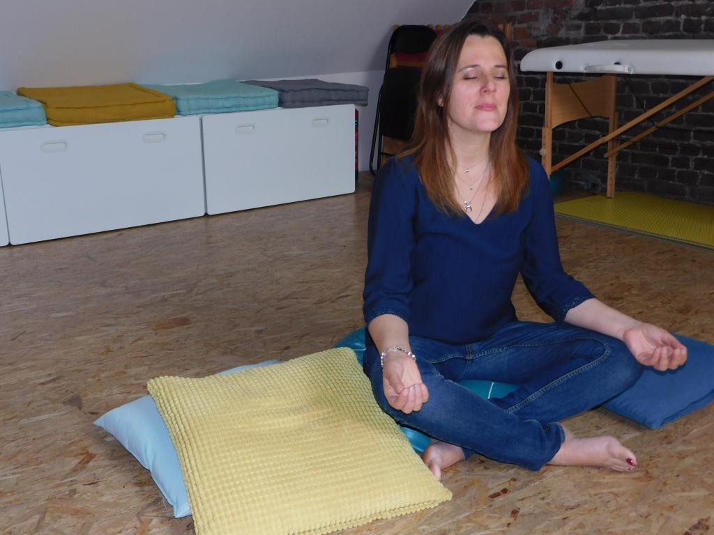 Fanny Caufriez de Courant Indigo est assise  sur un coussin de méditation, mains sur les genoux, yeux fermés !