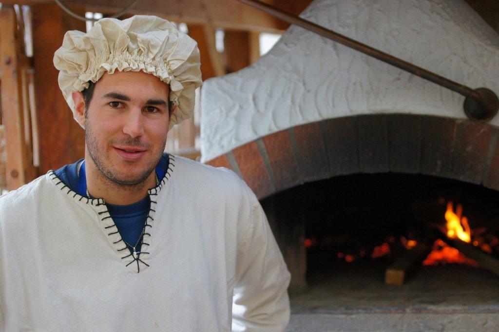 Un jeune boulanger pose devant son vieux four à pain.
