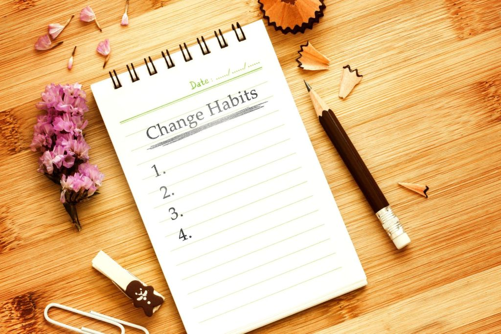 Un carnet de notes sur une table en bois où figure les 5 nouvelles habitudes que vous devez prendre après un licenciement