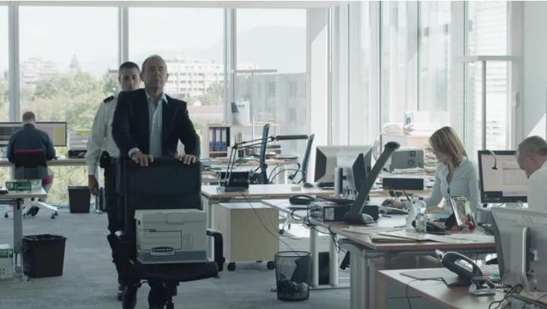 """Scène du film """"Ceux qui travaillent"""" où Olivier Gourmet pousse sa chaise de bureau dans un openspace parce qu'il a été viré de son entreprise."""