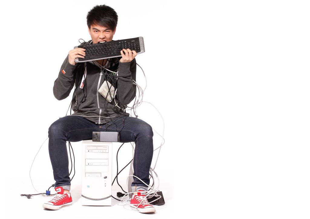 Un jeune homme assis sur la tour d'un ordinateur croque un bout de son clavier.