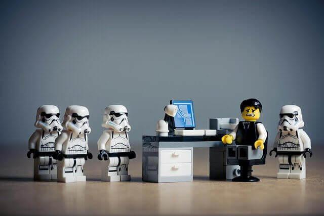 Quatre stormtroopers en légo encerclent le bureau d'un salarié crispé.