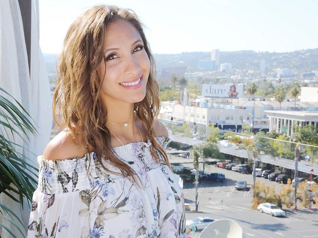 Kristel Khalil souriante pose dans un décor ensoleillé