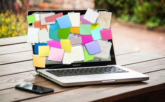 Un ordinateur avec plein de post it parce que la recherche d'emploi oblige à penser à tout.