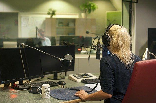 Une jeune femme blonde vue de dos parle dans un micro à la radio