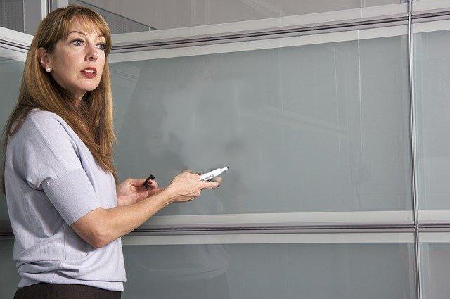 Une femme blonde debout devant un tableau dans une salle de réunion